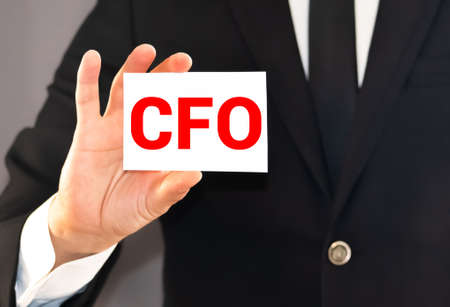 CFO letters or Chief Financial Officer on the card held by a man hand, vintage tone.