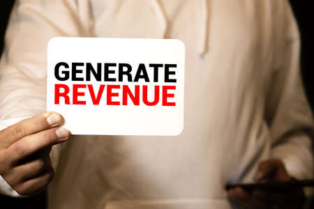 Card with text GENERATE REVENUE in the hand of a businessman. 版權商用圖片