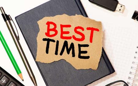 best TIME written in a notebook near a white alarm clock.