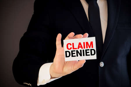 Businessman putting a card with text Claim Denied in the pocket.