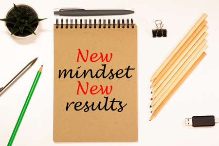 New mindset new results words letter, written on notepad, work desk top view. Motivational self development business typography quotes concept Reklamní fotografie