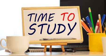 Alarm clock and blackboard with text Time to study on brown wooden background.