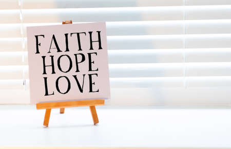 spiritual reminder or metaphysical concept - faith, hope and love handwritten on colorful notes and posted on cork bulletin board Stock fotó - 155438863