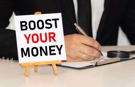 Handwriting text Boost Your Money. Concept meaning increase your bank saving using effective methods Paper clip and torn cardboard placed above a wooden classic table backdrop. Stock fotó - 155438902