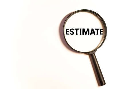 Estimates. The inscription on wooden blocks Through a magnifying glass on a blue background. Isolated.