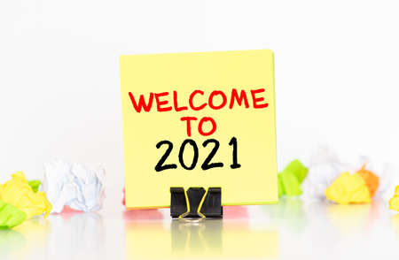 white paper with text Welcome 2021 on the blue background with a lot of another paper. Imagens
