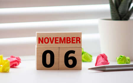 Closeup surface white wooden calendar with black 6 november word on blurred brown wood desk isolated on white background with copy space, selective focus at the calendar