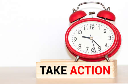 Take action now words written on wooden table with clock, dice, calculator pen and compass,