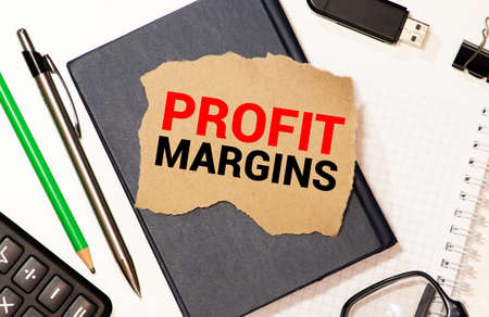 PROFIT MARGIN, on the tablet pc screen held by businessman hands - online, top view.