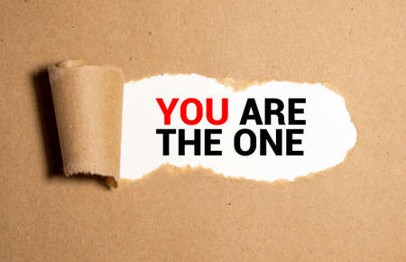 A man is holding a piece of paper which is saying 'You are the one'. The paper is white with black handwritten letters and the background is red.