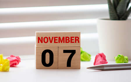 Closeup white wooden calendar with black 7 november word on blurred white wood desk and cream color wallpaper in room textured background with copy space, selective focus at the calendar Imagens
