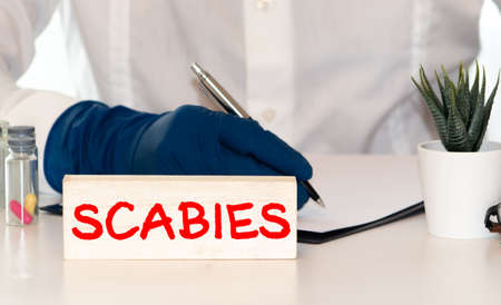 Word scabies on a white background with a syringe in hand. Medicine concept.