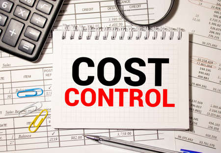 calculator with text COST CONTROL with white paper. Imagens