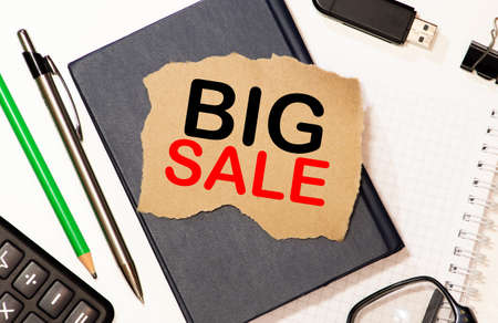 On a sheet of paper, the inscription BIG SALE is written to the letter tablet, next to the report Imagens