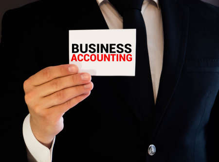 Finance and business concept. The businessman has on his desk graphs with reports, a notebook, a magnifying glass and a document with the inscription - BUSINESS ACCOUNTING