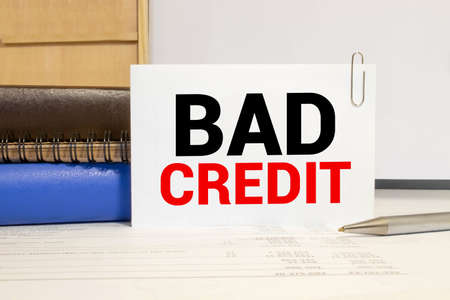 Word writing text Bad Credit. Business concept for inability of a demonstrating or company to repay a debt on time White pc keyboard with empty note paper and paper clips above white background. Imagens