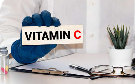 Doctor advises. Nutritionist or medical worker holds a VITAMIN C sign, healthy lifestyle concept