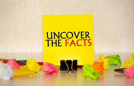 Uncover The Facts appearing behind wall. Concept Imagens