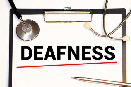 On a white background lies a stethoscope and the word DEAFNESS is written. Imagens