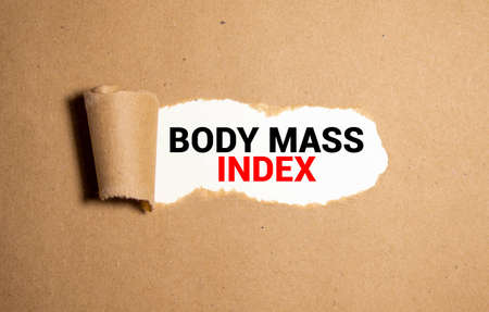 The text Body Mass Index appearing behind torn paper.