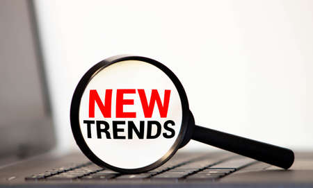 NEW TRENDS text written on magnifying glass. Main trend of changing something. Popular and relevant topics. New trends in business. Recent and latest trend. Evaluation methods.