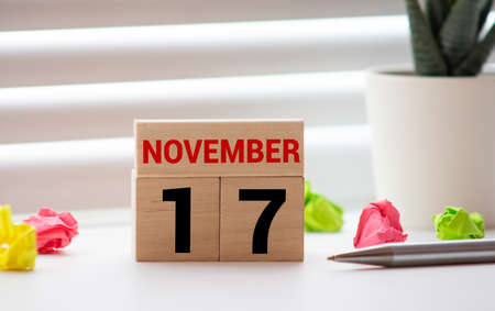 White block calendar present date 17 and month November on wood background.