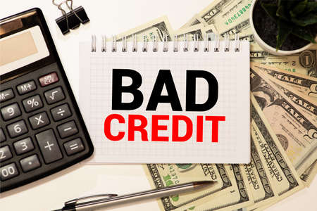 Word writing text Bad Credit. Business concept for inability of a demonstrating or company to repay a debt on time Trendy metallic laptop clips pencil squared paper sheet colored background. Imagens