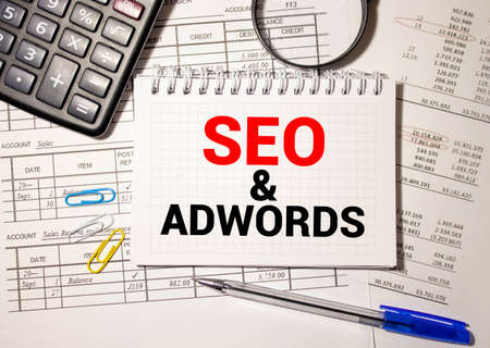 Word writing text Seo And Adwords. Business concept for Pay per click Digital marketing Google Adsense Locked diary sheets clips marker mouse alarm clock colored background. Imagens