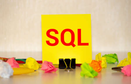The SQL label on the yellow business card from the daily planner. The blue diary and yellow pen are on the orange table.