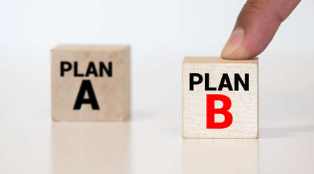 Time for Plan B. Hand is turning a dice and changes the word Plan A to Plan B.