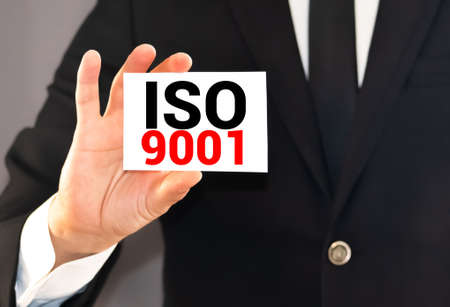 Message on the card ISO 9001, in hands of businessman.