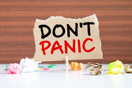 Word writing text Don t not Panic. Business concept for sudden strong feeling of fear prevents reasonable thought Clothespin holding blue paper note crumpled papers several tries mistakes. Фото со стока