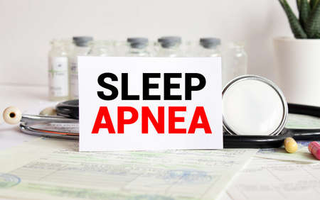 Stethoscope on wood with Sleep Apnea words as medical concept.