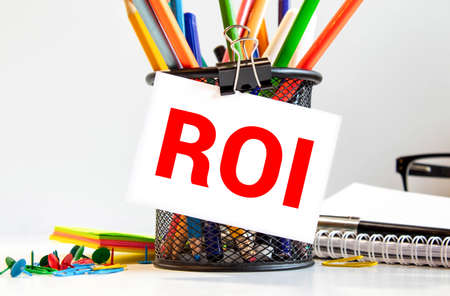 ROI Return On Investment acronym on yellow sticky note Banco de Imagens