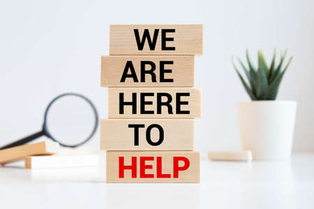 Wooden blocks with text 'we are here to help'. Beautiful white background, copy space. Business concept