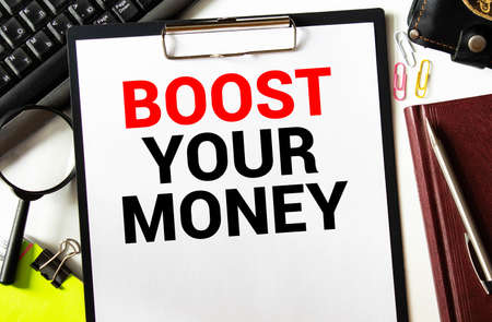 Text sign showing Boost Your Money. Conceptual photo increase your bank saving using effective methods. Text written in notebook with pen, calculator, magnifier and dollars background.
