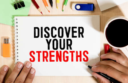 Discover your strengths- business concept of entrepreneur management message on wood background with paper clips.