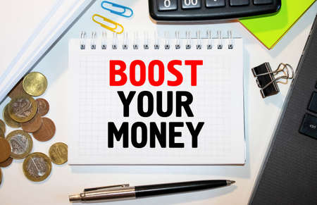 Handwriting text Boost Your Money. Concept meaning increase your bank saving using effective methods Paper clip and torn cardboard placed above a wooden classic table backdrop.