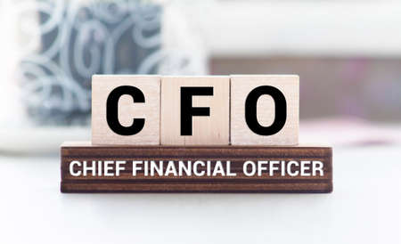 CFO Chief Financial Officer written on a wooden cube in front of a laptop.