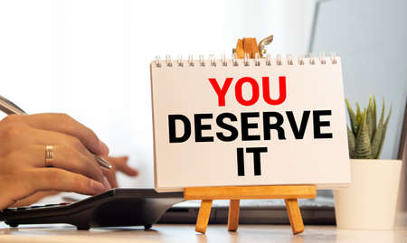 Word writing text You Deserve It. Business concept for Reward for something well done Deserve Recognition award Blacky wooden desk laid paper clip randomly one hold yellow board with text. Foto de archivo