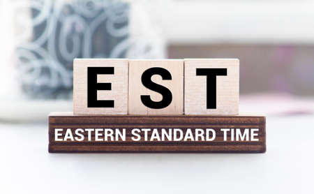 Alphabet letter in word EST abbreviation of established, estimated, eastern time zone, expressed sequence tag on wood background