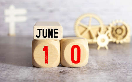 Wooden calendar June 10 on a white background close up.