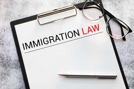 Book with words Immigration Law and glasses Stock Photo