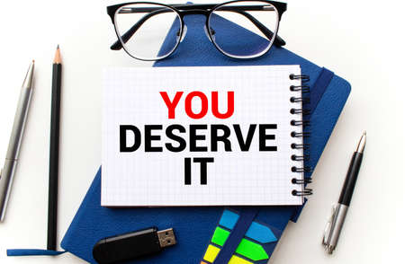 Text sign showing You Deserve It. Conceptual photo Reward for something well done Deserve Recognition award Paper blue desk computer keyboard office study notebook chart numbers memo.