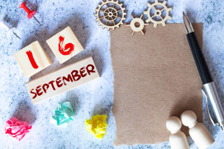 Gift box and wooden calendar with trendy blue numbers, September 16, business planner Reklamní fotografie