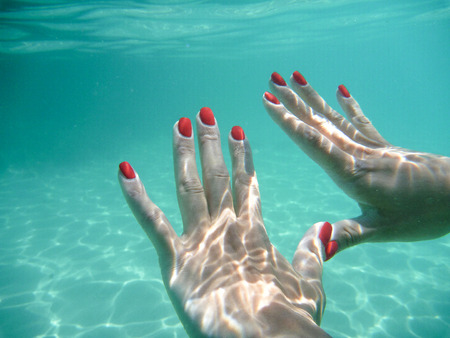 nails: girl snorkeling in blue water Malta showing fingers underwater Stock Photo