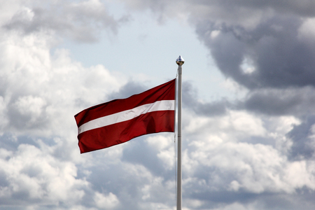 flag of the latvia on blu sky with clouds Stock Photo