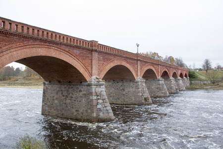 old Brick bridge across the River Venta in the city of Kuldiga Latvia