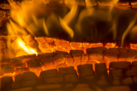 burning firewood coal closeup in the fireplace. Fire fireplace ember wood home Embers closeup. Glowing embers in hot red color. Stock Photo