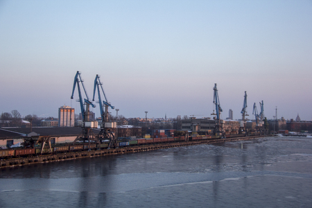 Freight shipping containers and gas oil tanks at the docks. in import export and business logistic. Cargo ship docked at at the port. Cargo cranes by winter evening in the Port Riga, Latvia. Editoriali